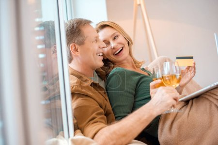 Photo pour Lunettes tenue couple de vin blanc en riant tout en étant assis par la fenêtre à la maison - image libre de droit