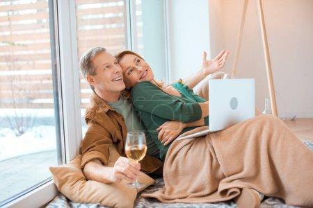 Photo pour Couple excité assis sur le sol à la nouvelle maison et en utilisant un ordinateur portable - image libre de droit
