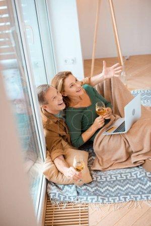 Photo pour Couple excité en levant tandis qu'assis sur le plancher à la nouvelle maison et à l'aide d'ordinateur portable - image libre de droit