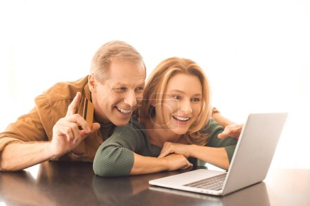 Photo for Smiling man showing idea sign while using laptop with wife on white background - Royalty Free Image