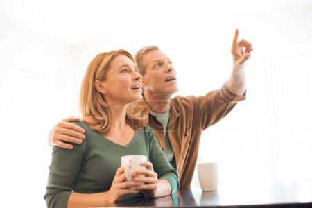 Photo pour Homme pointer avec le doigt tout en étreignant épouse avec une tasse de café dans les mains - image libre de droit