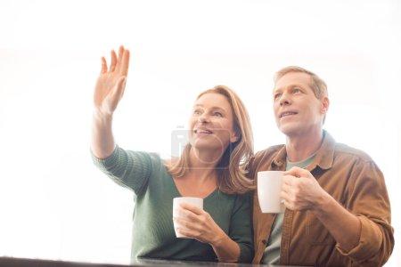 Photo pour Sourire de pointage main de femme tout en se tenant près de mari - image libre de droit