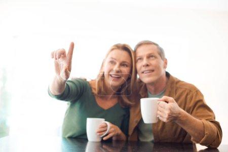 Photo pour Mise au point sélective du couple tenant des tasses à café tout en pointant avec le doigt de femme - image libre de droit