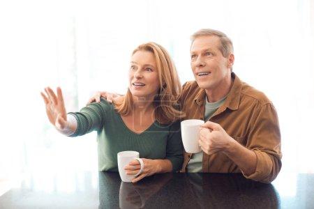 Photo pour Mise au point sélective du couple tenant des tasses à café tout en pointant avec la main de femme - image libre de droit