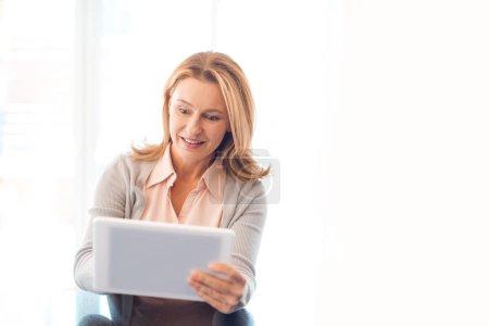 Photo pour Jolie femme blonde souriante utilisant une tablette numérique - image libre de droit
