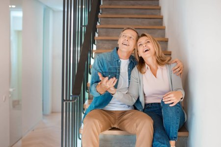 Photo for Happy couple embracing while sitting on stairs at new home - Royalty Free Image