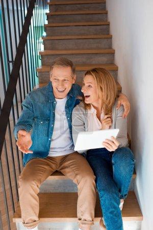Photo pour Couple souriant talking en assis dans les escaliers ou à l'aide de tablette numérique - image libre de droit