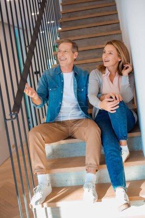 Photo pour Heureux couple assis sur les escaliers de la maison neuve - image libre de droit