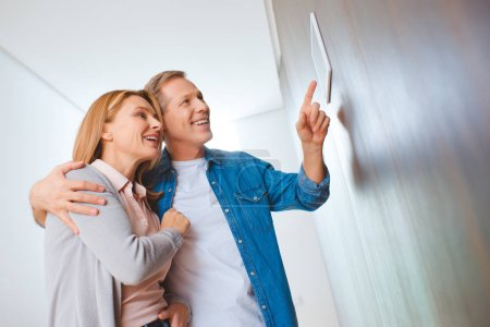 Photo for Smiling man pointing at smart home control panel while hugging wife - Royalty Free Image