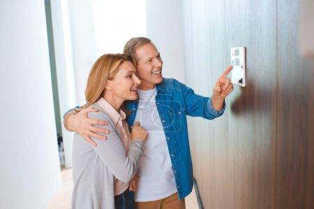 Foto de Hombre feliz apuntando a panel de control Inicio inteligente y mujer abrazando - Imagen libre de derechos