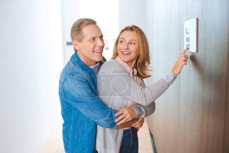 Photo for Happy man hugging wife using smart home control panel - Royalty Free Image