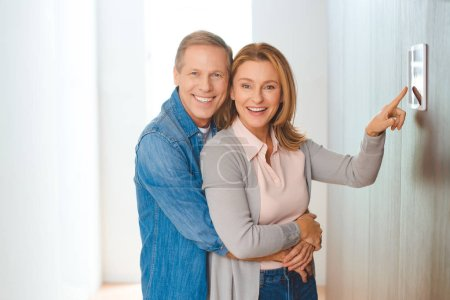 Photo for Smiling husband hugging wife pointing at smart home control panel - Royalty Free Image
