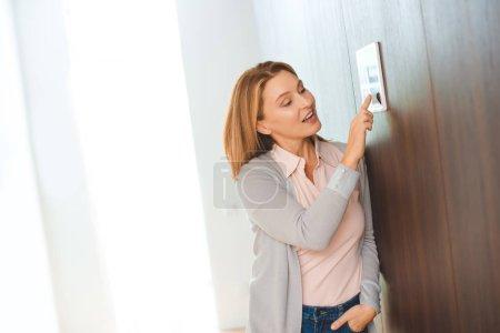 Photo pour Jolie blonde femme à l'aide du panneau de maison intelligente - image libre de droit