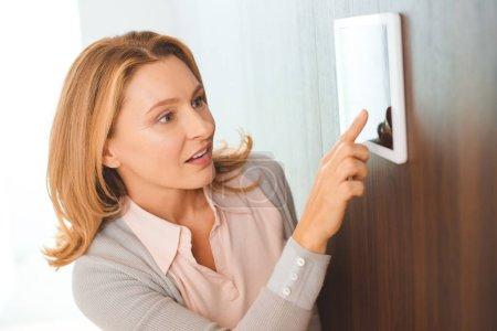 Foto de Mujer muy rubia con panel de control Inicio inteligente - Imagen libre de derechos