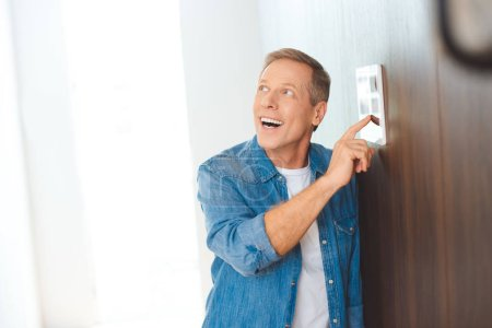 Photo for Excited handsome man using smart home control panel - Royalty Free Image