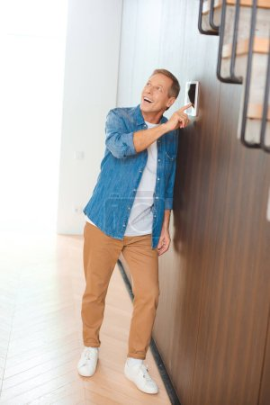 Photo for Excited handsome man using smart house control panel at new home - Royalty Free Image