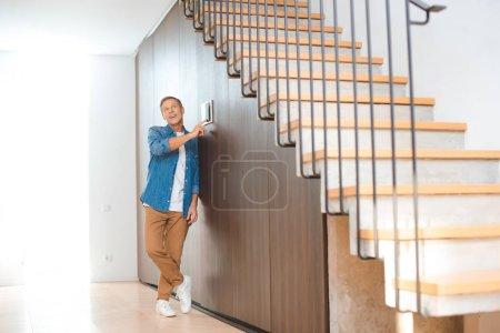 gut aussehender Mann mit Smart-House-Bedienfeld im neuen Zuhause