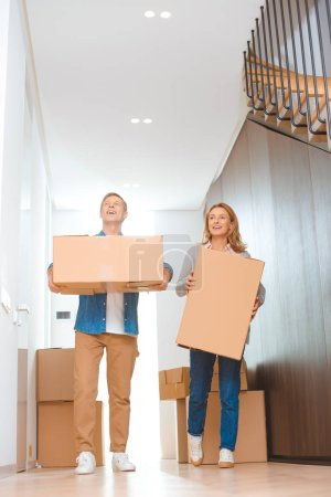 Photo for Happy couple holding cardboard boxes at new home - Royalty Free Image