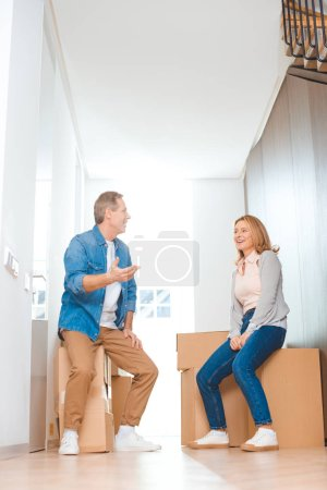 Photo for Happy couple talking while sitting on cardboard boxes at new home - Royalty Free Image
