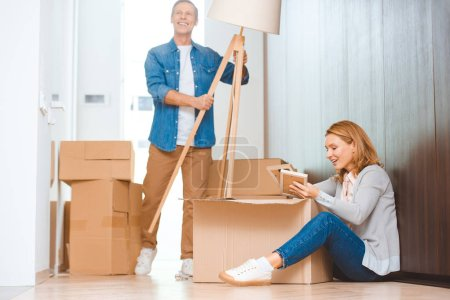 Photo for Smiling man holding floor lamp while woman sitting in floor and unpacking carton box - Royalty Free Image