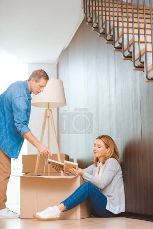 Photo for Woman sitting on floor and unpacking cardboard box and man pointing with finger - Royalty Free Image