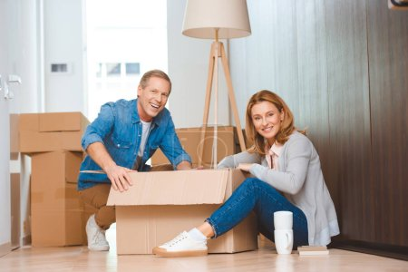 Photo for Happy couple sitting on floor and unpacking cardboard box - Royalty Free Image