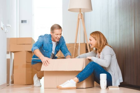 Photo for Cheerful couple sitting on floor and unpacking cardboard box - Royalty Free Image