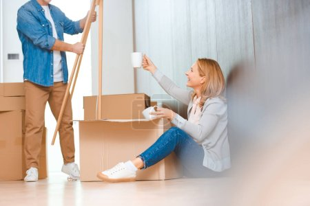 Photo for Selective focus of woman sitting on floor and unpacking cardboard box - Royalty Free Image