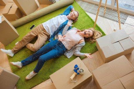 Photo pour Heureux couple allongé sur le sol sur tapis vert entouré de boîtes en carton - image libre de droit