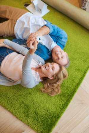 Photo for Selective focus of woman holding keys with house model trinket while lying on green carpet with smiling husband - Royalty Free Image