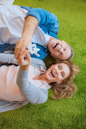 Photo for Selective focus of excited couple holding keys with house model trinket while lying on green carpet - Royalty Free Image