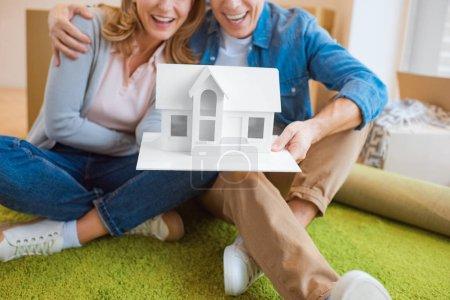 selektiver Fokus glückliches Paar hält Hausmodell, während es auf grünem Teppich sitzt