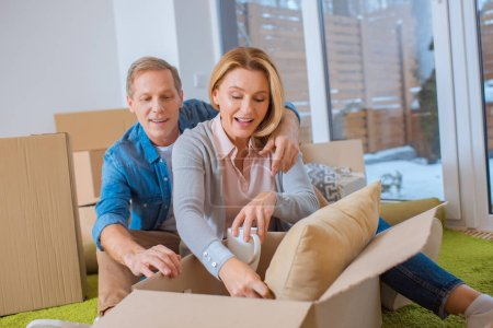 Photo for Happy couple unpacking carton boxes at new home - Royalty Free Image
