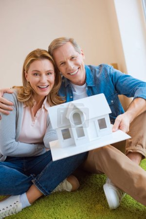 couple heureux démontrant modèle de maison tout en regardant caméra