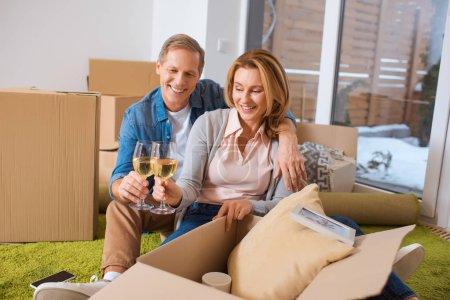 Photo pour Lunettes de tintements heureux couple de vin blanc tout en se reposant de boîtes en carton - image libre de droit