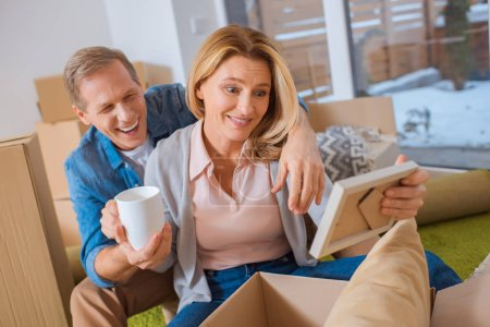 Photo for Cheerful couple unpacking cardboard box at new home - Royalty Free Image
