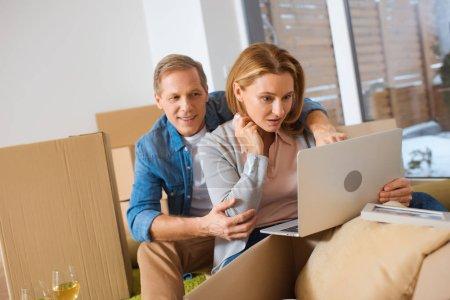 Photo pour Couple à l'aide d'ordinateur portable tout en restant assis près des boîtes de carton à la nouvelle maison - image libre de droit