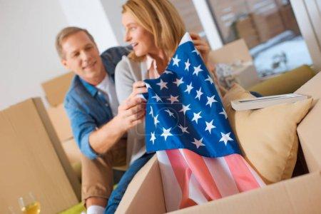 Photo pour Mise au point sélective de femme sortir de la boîte en carton drapeau usa - image libre de droit