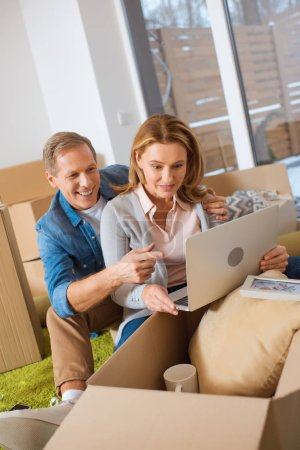 Photo for Smiling couple using laptop while sitting near carton boxes at new home - Royalty Free Image