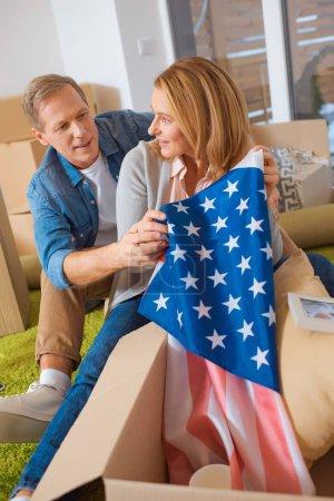 Photo pour Femme, drapeau usa sortir de la boîte en carton tout en restant assis près de mari - image libre de droit