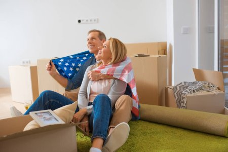 Photo for Happy couple wrapped in usa national flag looking up while sitting near cardboard boxes at new home - Royalty Free Image