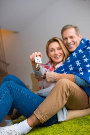 Photo for Selective focus of happy woman holding keys with house model trinket while wrapping in usa national flag with husband - Royalty Free Image