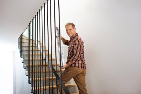 Foto de Sonriente hombre guapo va arriba y llevando la imagen - Imagen libre de derechos