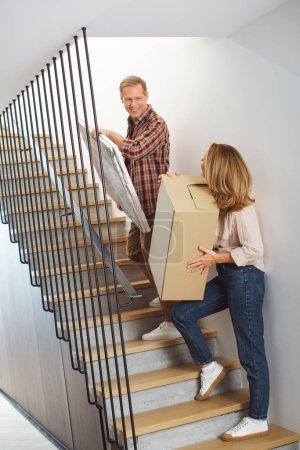 Photo pour Femme avec boîte en carton et l'homme avec l'image va à l'étage - image libre de droit
