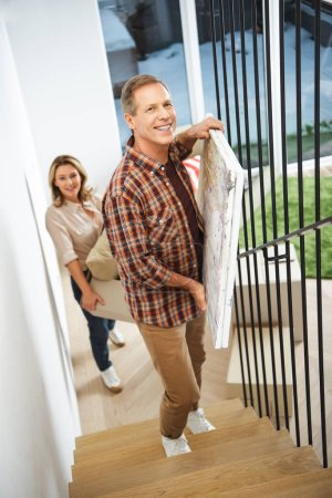 Photo for Selective focus of smiling couple carrying things upstairs and looking at camera - Royalty Free Image