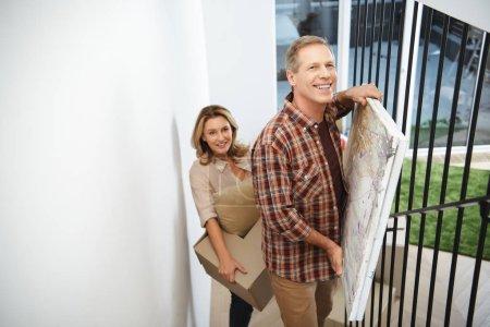 Photo pour Mise au point sélective de l'heureux couple transportant des choses à l'étage et en regardant la caméra - image libre de droit