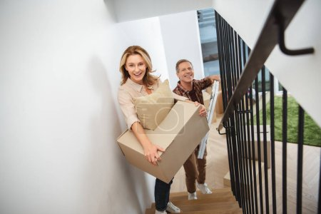 Photo for Smiling happy couple carrying things upstairs and looking at camera - Royalty Free Image