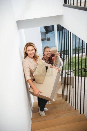 Photo pour Femme avec homme avec photo va à l'étage et en regardant la caméra et boîte de carton - image libre de droit