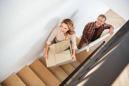 Photo pour Smiling couple porte des choses à l'étage à nouveau accueil - image libre de droit