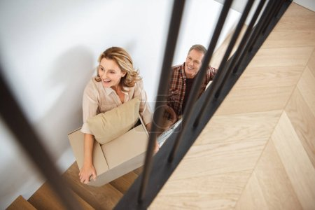 Photo pour Mise au point sélective du couple porte des choses à l'étage à la nouvelle maison - image libre de droit